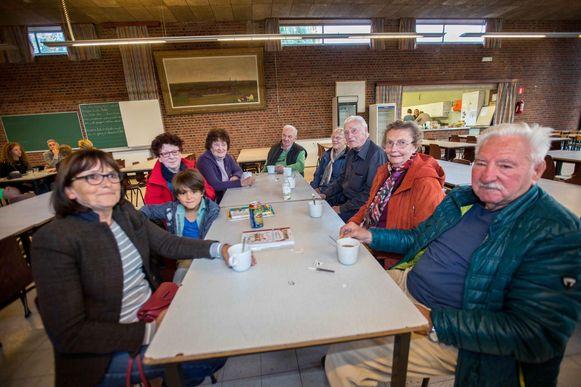 Enkele buurtbewoners wachten bij een kop koffie geduldig op meer nieuws in de gemeenteschool.