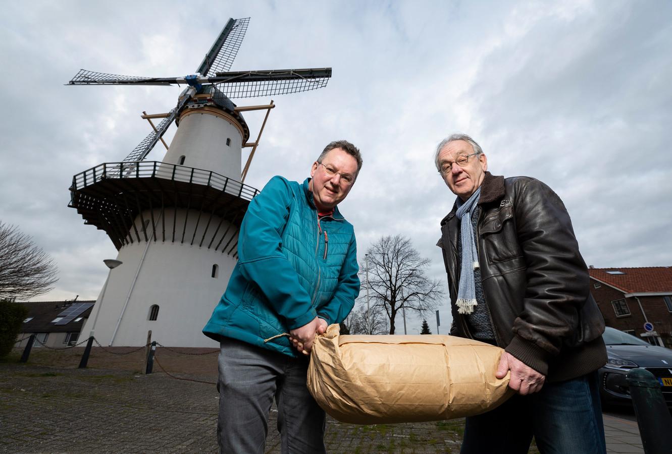 Cor Groen (blauwe jas) en Jacques Boonekamp van Stichting Molen De Hoop lopen met een 25 kilo zak meel.