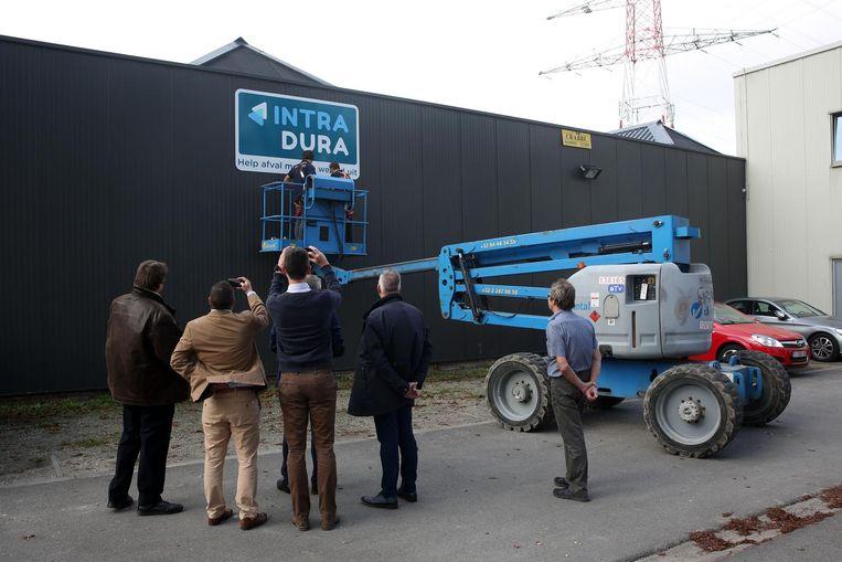 De leden van de raad van bestuur van Intradura nemen foto's, terwijl het nieuwe logo wordt opgehangen aan de site in Drogenbos.