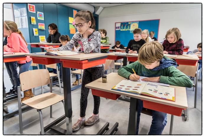De leerlingen van groep 6 van de Lorentzschool in Leiden experimenteren met tafels waar ze aan kunnen staan. Isabelle vindt het fijn om even te bewegen, Hugo zit liever tijdens de rekenles.