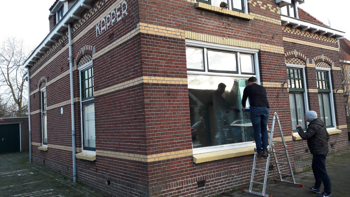 Peter Peters van Point O plakt maandagochtend folie op het raam. Daartegen wordt van binnenuit het logo van Schon Pekske geprojecteerd.