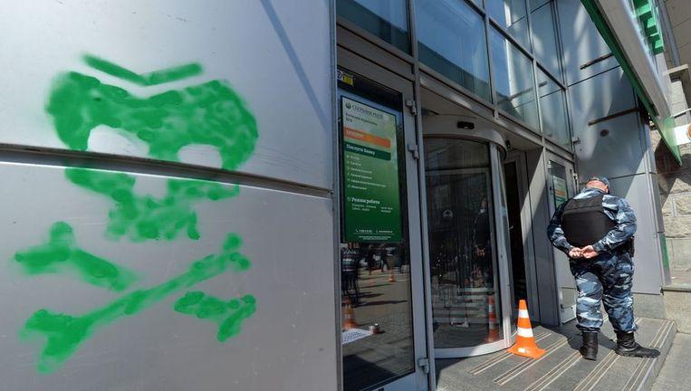 Demonstranten hebben een doodshoofd getekend op een muur van de Russische Sberbank in Simferopol. Beeld afp
