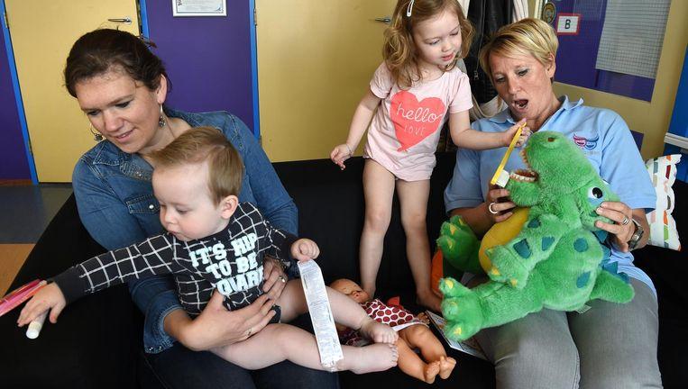 Roos (3) leert met behulp van een knuffel hoe zij haar tanden moet poetsen van mondzorgcoach Kiki van Winkel. Beeld Marcel van den Bergh / de Volkskrant