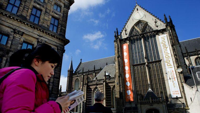 Een toerist staat voor de Nieuwe Kerk op de Dam. Beeld anp