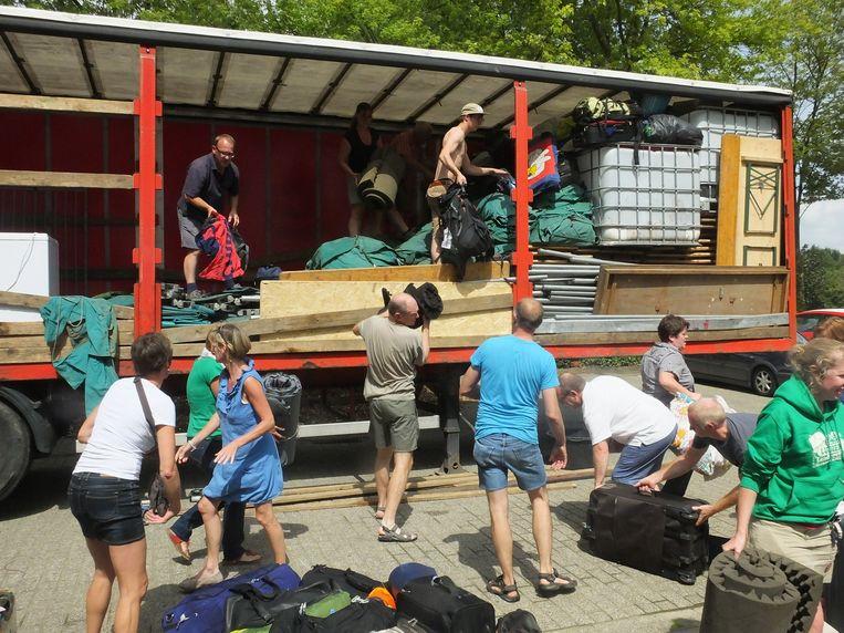 De ouders helpen mee de materiaalwagen leegmaken.
