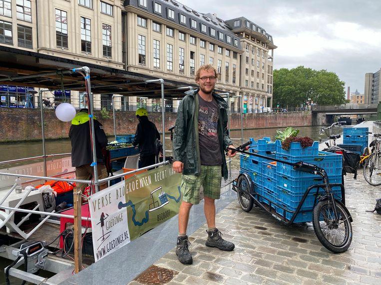 Wim Michels van bioboerderij Goedinge, tussen de bioboot en een fietskar.
