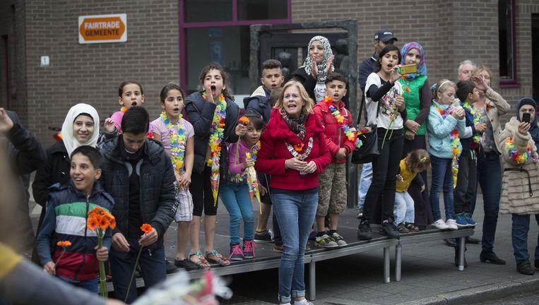 De asielzoekerskinderen in Leusden die niet mee mochten, onthalen op het podium bij de burgemeester donderdag de wandelaars. Beeld null