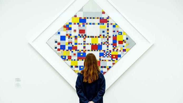Een bezoekster bekijkt het schilderij Victory Boogie Woogie van de kunstschilder Piet Mondriaan in het Gemeentemuseum.