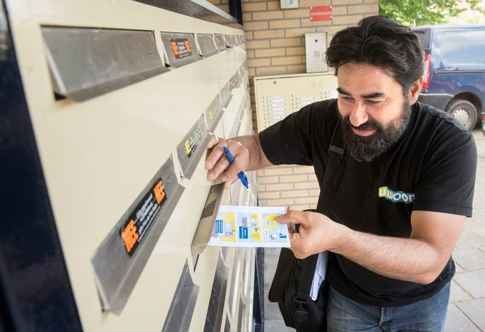 Medewerker Ahmet Nazligul stopt een 'ik trof u niet thuiskaartje' nieuwe stijl (met icoontjes) in de brievenbus bij een client.