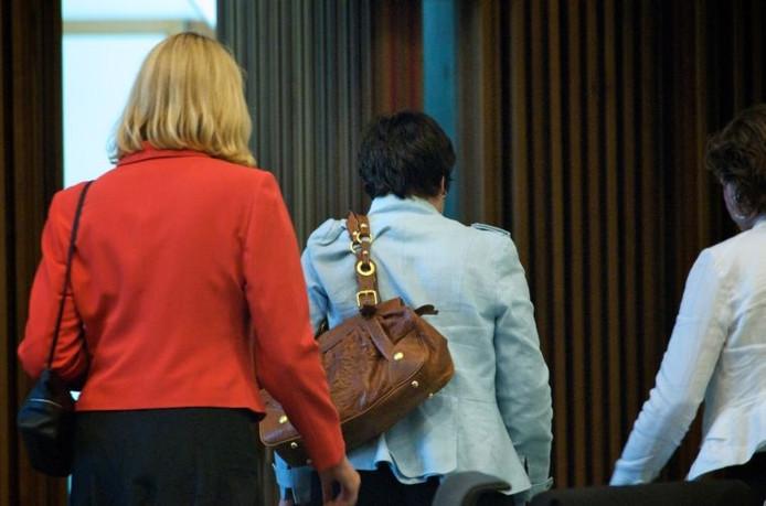 Rita Weeda (midden) verlaat samen met burgemeester Krikke de Arnhemse raadzaal na haar aftreden. foto Marc Pluim