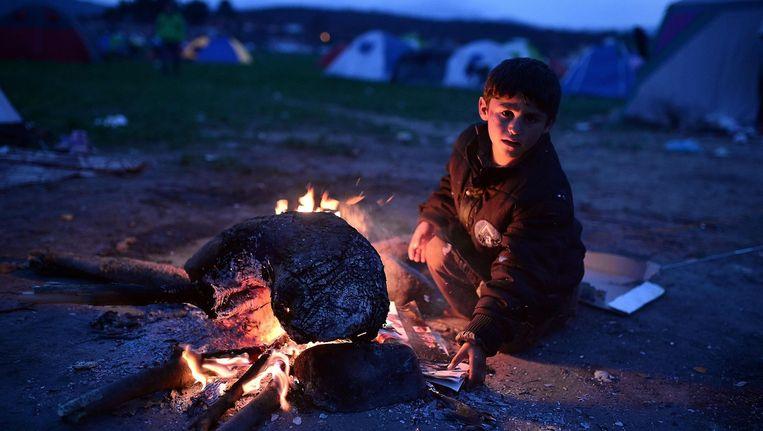 Een jongen warmt zich bij een vuurtje in Idomeni, waar duizenden vluchtelingen zijn gestrand. Beeld afp