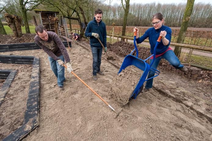 Vrijwilligers verbeteren de kampvuurkuil bij Scouting Zetten.