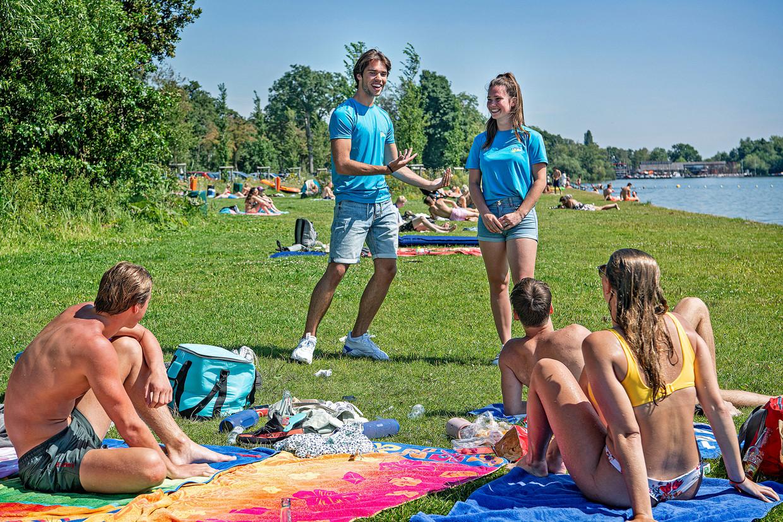 Daphne en Lars wijzen jongeren op de anderhalve meter.  Beeld Guus Dubbelman / de Volkskrant
