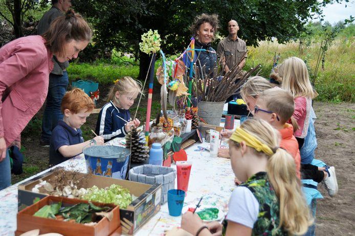 Aan een grote knutseltafel in het Voedselbos konden kinderen onder begeleiding van Sarah van Genugten (midden achter) verven en knutselen met takken.