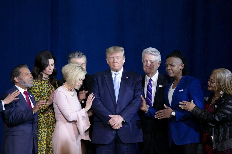 Trump biddend met christelijke aanhangers. Beeld Bloomberg via Getty Images