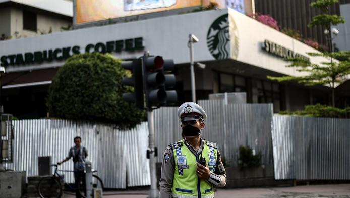 Een politieagent voor de beschadigde Starbucks-locatie in Jakarta.