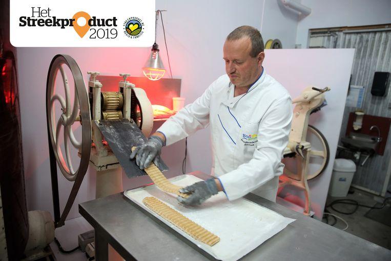De snoepjes worden nog steeds gemaakt met een oude machine, zo demonstreert Johnny Sterck.