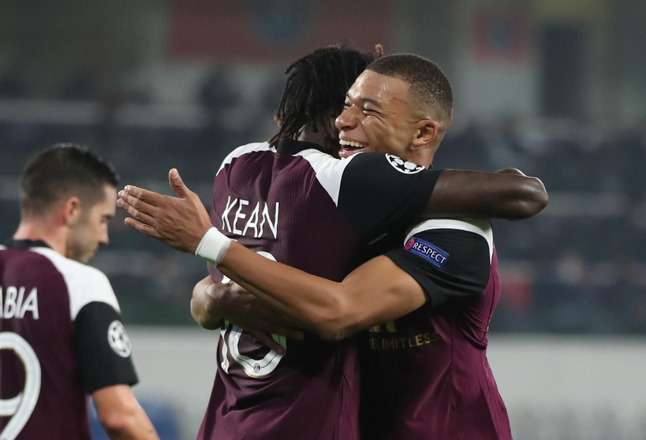 Moise Kean en Kylian Mbappe vliegen elkaar in de armen.