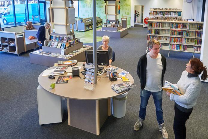 De vernieuwde bibliotheek in Heeswijk-Dinther. Rechts de boeken, links de open ruimte met de verrijdbare meubels. Rechts op de foto Florian de Visser en Agnes Setrojojan met elkaar in overleg over de laatste dingen die nog gedaan moeten worden voor de opening op vrijdag 17 januari.