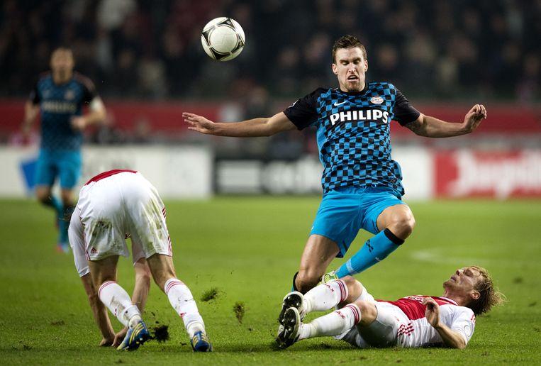 Kevin Strootman van PSV stuit op Christian Poulsen. Ajax wint in de Eredivisie thuis in de Arena met 3-1 van PSV. Beeld anp