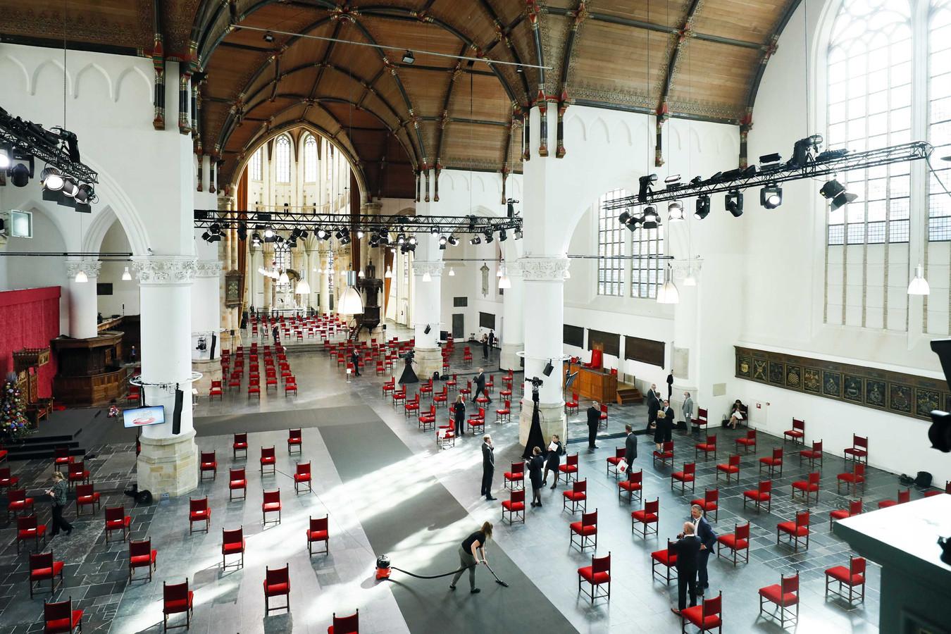 De grijze loper wordt uitgebreid gestofzuigd voor de Grote Kerk de deuren opent voor Kamerleden, ministers en het koninklijk paar.