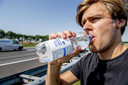 Een gestrande reiziger drinkt water langs de snelweg. Automobilisten wordt aangeraden om extra water mee te nemen voor onderweg.