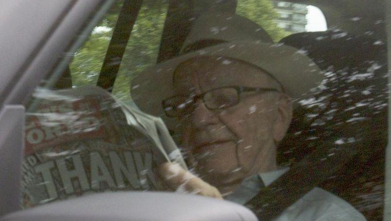 Rupert Murdoch leest News of the World terwijl hij naar het hoofdkwartier van die krant in Londen wordt gereden. Beeld reuters