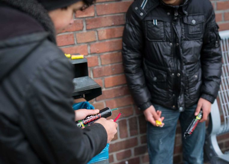 wee jongens spelen met cobra-vuurwerk op straat. Beeld anp