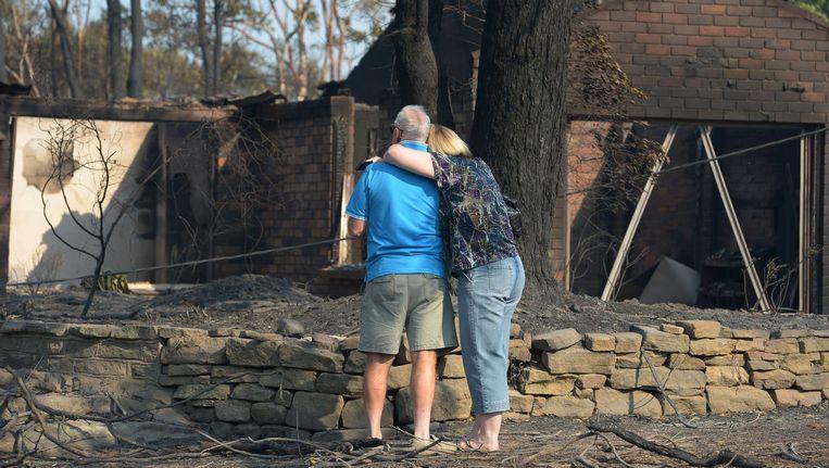 Een echtpaar aanschouwt de resten van zijn uitgebrande woning in Winmalee, in de Blue Mountains ten westen van Sydney. Beeld AFP