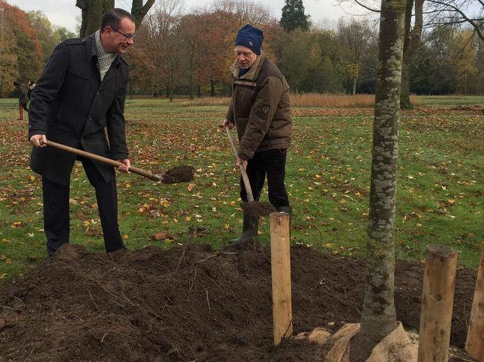 Wethouder Mario Jacobs (l) en bioloog Henk Moller Pillot planten samen een hangende zilverlinde ter gelegenheid van de tachtigste verjaardag van het Tilburgse Leijpark.