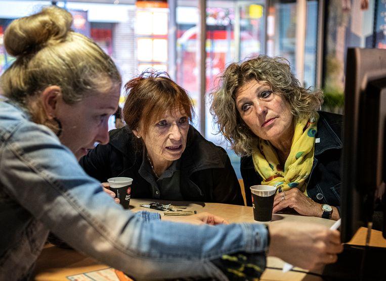 Gerrie Verwaaijen (midden) en Ria Dinnissen (rechts) overleggen met reisadviseur Debbie van den Tillaart. Beeld Koen Verheijden
