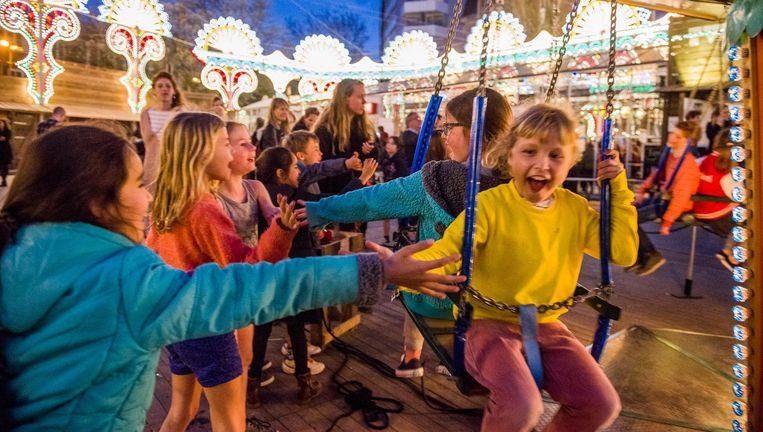 Vrolijk publiek met daarachter de lichtgevende sierbogen uit Zuid-Italië die op Festival Tweetakt te zien zijn. Beeld Jelmer de Haas