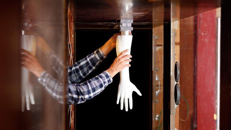 Een technicus monteert een testhand in een windtunnel. De vingers staan 10 graden uit elkaar, de optimale houding. Beeld TU Eindhoven/Bart van Overbeeke