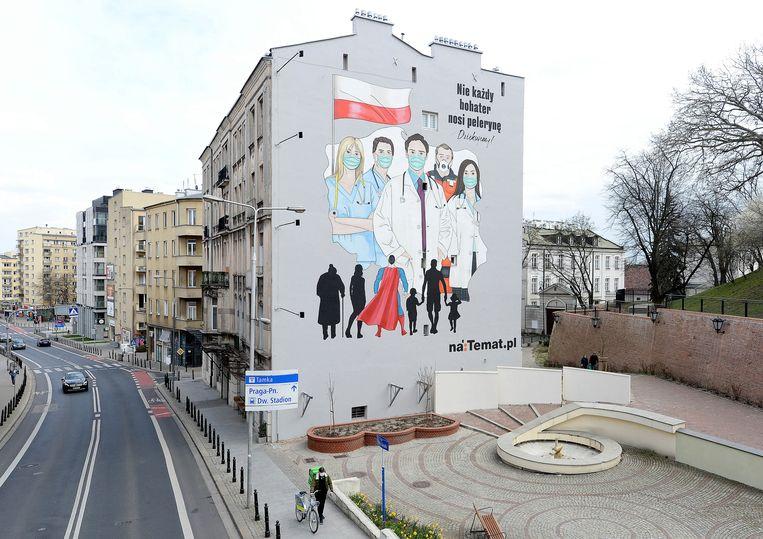 Een muurschildering om zorgverleners te bedanken in Warschau. De Polen zitten thuis, maar toch wil de regering dat de verkiezingen op 10 mei doorgaan – per post. Beeld AP