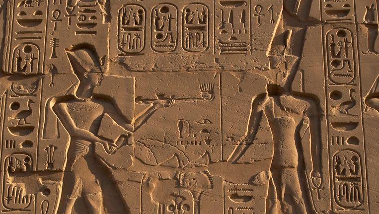 Reliëf uit de tempel van Amon in Egypte met daarop een afbeelding van farao Ramses II (links) die een geuroffer met kyphi brengt aan de god Amon. Beeld Getty Images