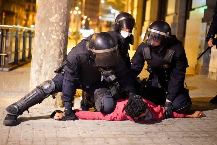 Een demonstrant wordt na het geweld in Barcelona door politieagenten gearresteerd.