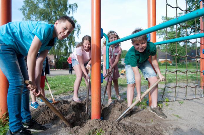 Kinderen zetten de schop in de grond om de laatste oude toestellen uit de speeltuin aan de Korenkamp in Epse te verwijderen.
