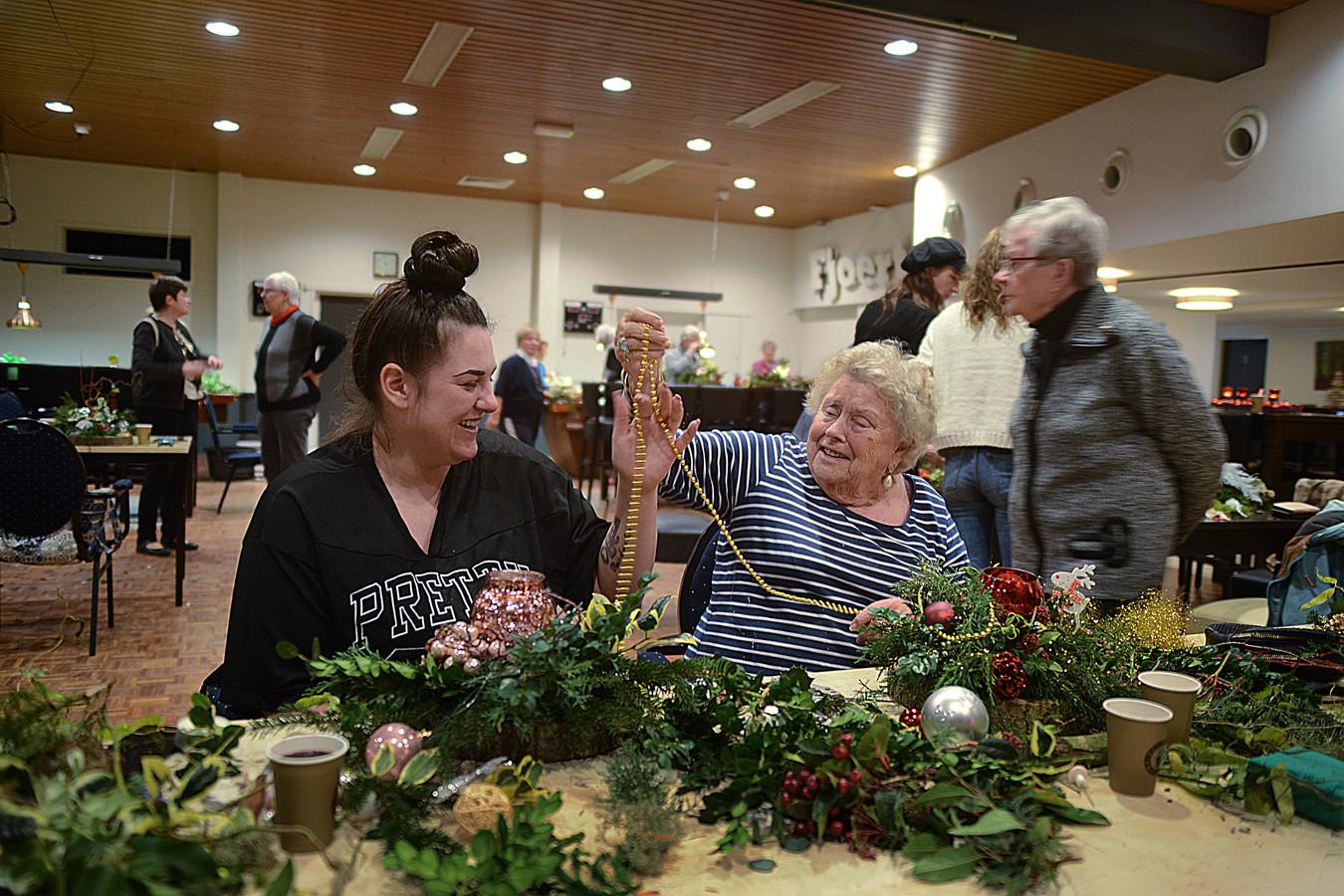 Shannen Visser en haar oma Ria Koers hebben een hoop lol samen tijdens het maken van hun kerststukje
