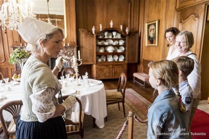 In stijl geklede vrijwilligers van Huis Singraven vertellen de bezoekers van de open dag hoe het er vroeger aan toe ging.