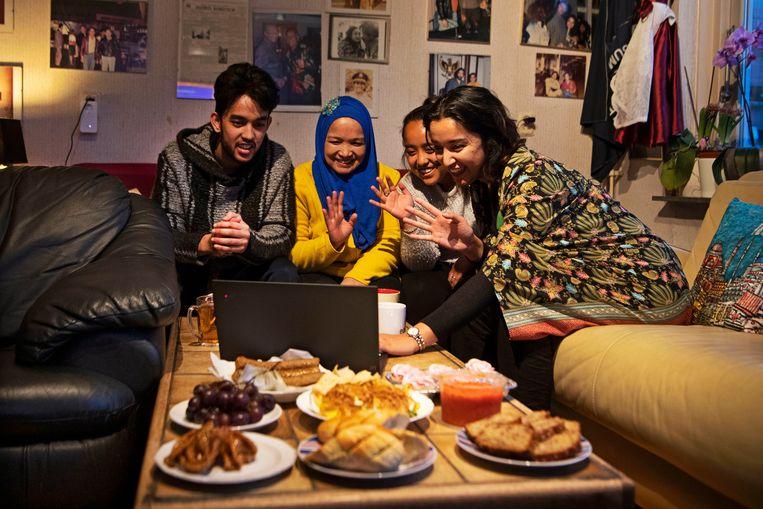 Iftarmaaltijd bij Dimple Sokartara (R), haar moeder, zusje en broertje. Via Zoom zijn er nog meer mensen virtueel aanwezig bij het verbreken van het vasten. Beeld Olaf Kraak
