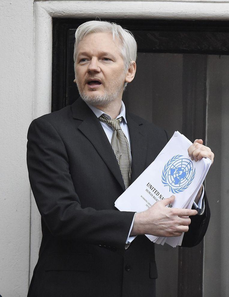 Assange op het balkon voor de ambassade van Ecuador in Londen, hij houdt het VN-rapport vast Beeld epa