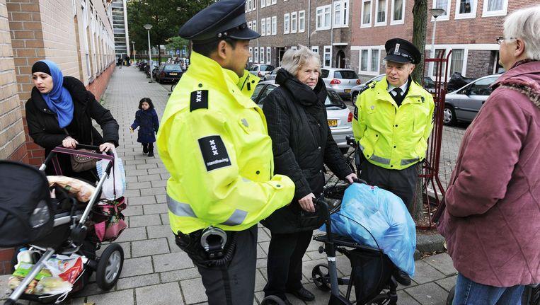 Handhavers praten in Amsterdam-Oost met buurtbewoonsters. Beeld Guus Dubbelman