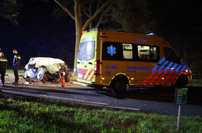 Ambulance en politieagenten bij de auto na het ongeluk.