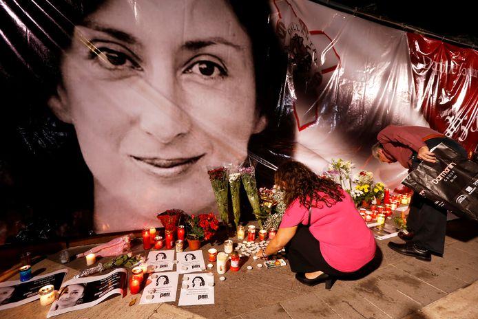 Bloemen en kaarsjes voor een grote afbeelding van de vorig jaar vermoorde Daphne Caruana Galizia