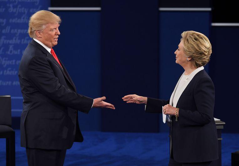 Trump en Clinton schudden elkaar de hand na afloop van een debat.  Beeld AFP