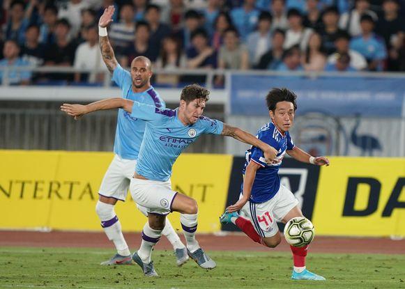 Koji Miyoshi (r) eind juli in Japan tijdens een oefenduel tegen Manchester City en John Stones.