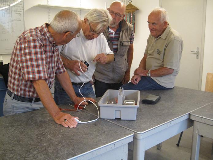 Andries Bongers (in wit shirt) probeert een elektrische notenkraker weer aan de praat te krijgen.
