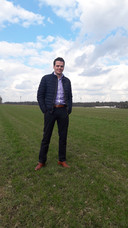 Thijs van Oirschot op het perceel in Haghorst waar hij een groot zonnepark wil bouwen. Op de achtergrond twee van de vier windmolens langs de A58 bij Spoordonk.