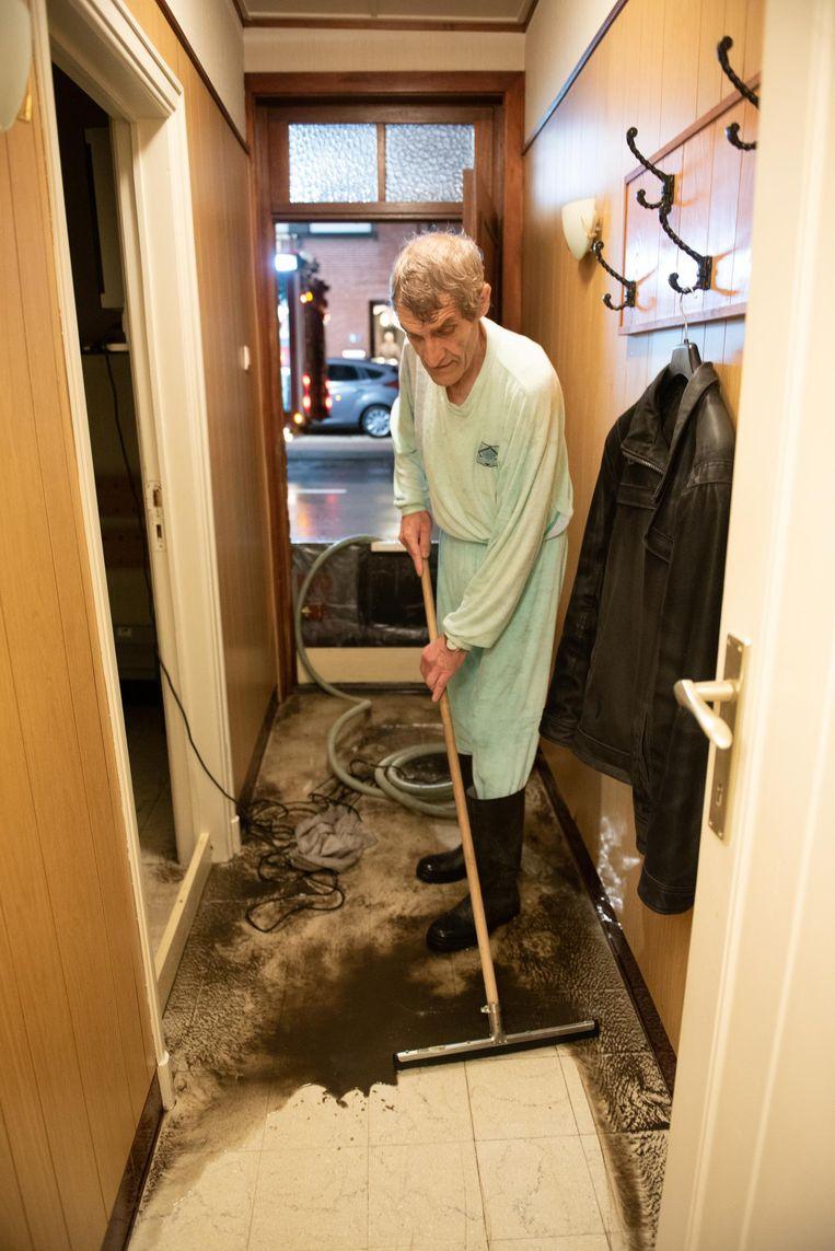 Dirk Pandelaere trekt het water en slijk uit zijn woning.
