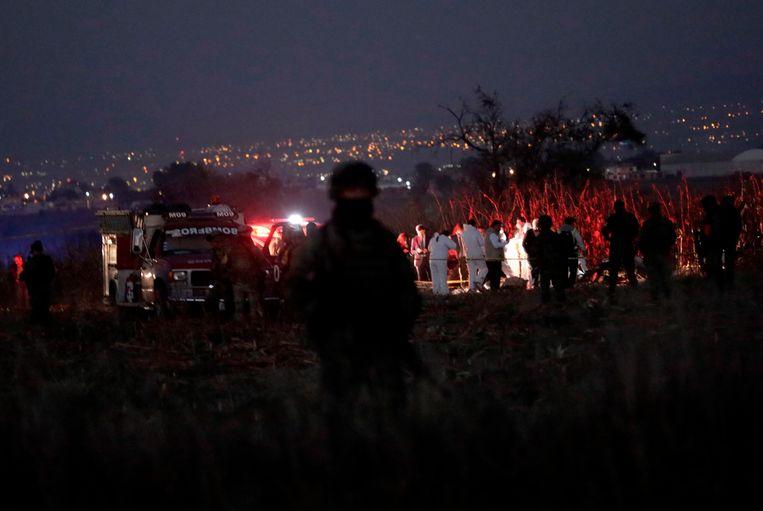 Hulpverleners bij het wrak van de gecrashte helikopter nabij Puebla. De Mexicaanse president opent een onderzoek naar het ongeval.